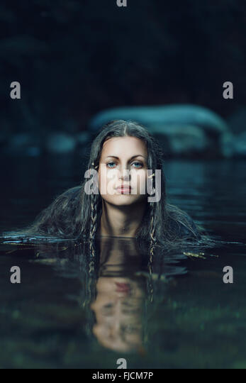 Beautiful water nymph in dark cyan stream . Ethereal and fantasy - Stock-Bilder