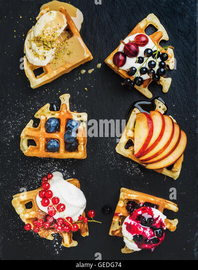 Warm belgian homemade waffles with fresh garden berries, fruit and ice cream on dark slate stone background - Stock Image