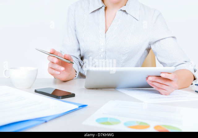 Relaxed businesswoman wearing casual shirt sitting at desk and working with data on digital tablet in the office - Stock-Bilder