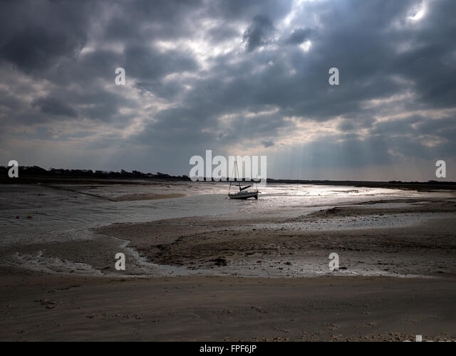Beached yacht at low tide in a sandy creek by East Head, West Wittering, West Sussex - Stock Image