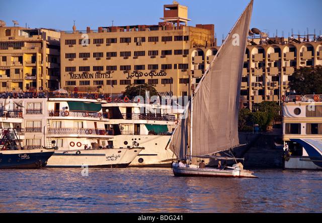 Felucca traditional wooden sailboat on Nile River Aswan Egypt city skyline nile cruise ships background - Stock Image