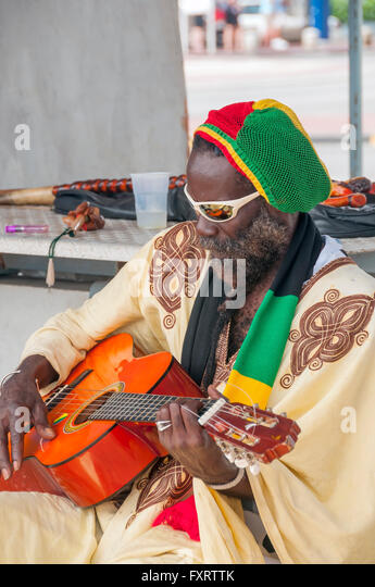 Man colorfully dressed plays guitar Willemstad Curacao - Stock Image