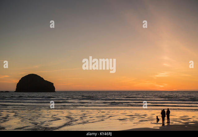 People on the beach to watch the sunset at Trebarwith Strand in Cornwall, England, UK - Stock Image