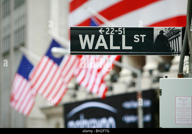 Wall Street and the New York Stock Exchange in New York with a huge American flag - Stock Image