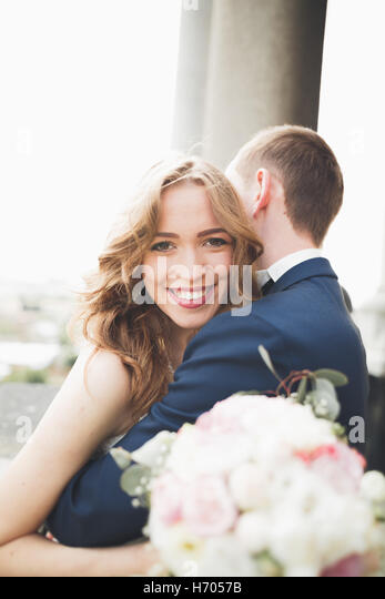 Stylish beautiful wedding couple kissing and hugging on background panoramic view of the old town - Stock Image
