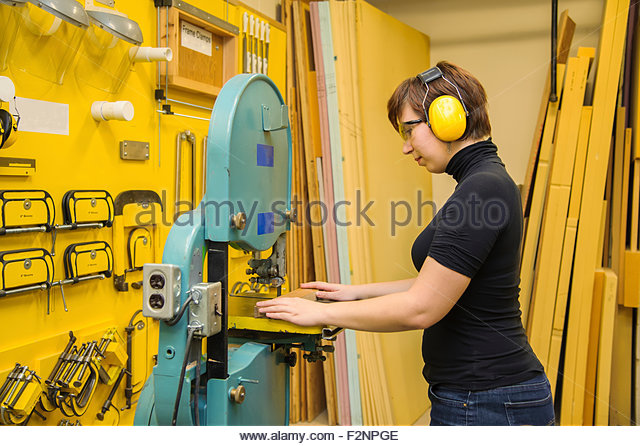 Caucasian woman operating machinery in workshop - Stock-Bilder