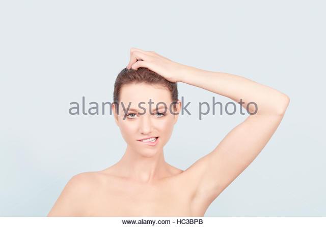Portrait of young woman scratching her head. - Stock-Bilder
