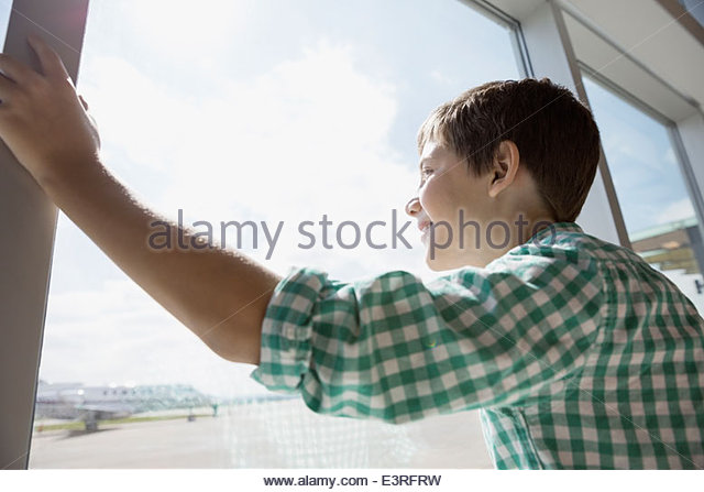 Boy looking at airport window - Stock Image