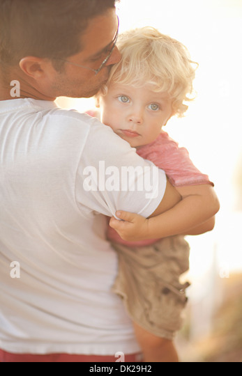Father carrying toddler son and comforting by kissing forehead - Stock Image