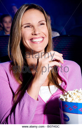 Woman enjoying a film at the cinema - Stock-Bilder