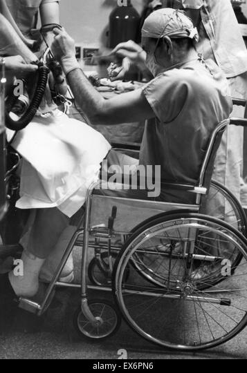 American surgeon Henry Swan II (1913-1996)Henry Swan performing surgery from a wheelchair 1960. Swan pioneered the - Stock Image