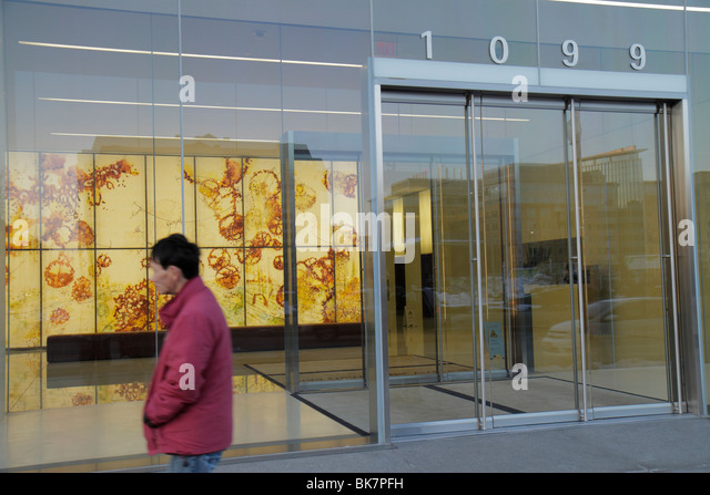Washington DC New York Avenue NW office building glass doors light mural corporate art lobby Asian man - Stock Image