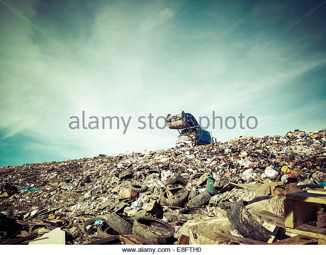 Garbage trunk dumping waste on landfill - Stock Image
