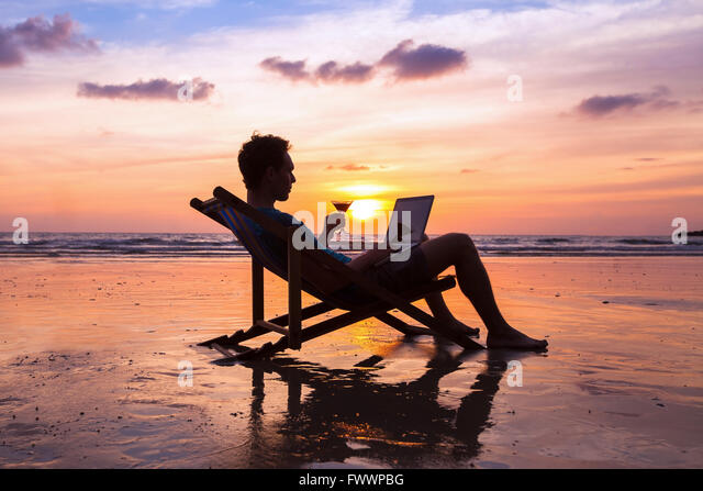 silhouette of successful business man reading emails on laptop on the beach at sunset, freelance job concept, work - Stock Image