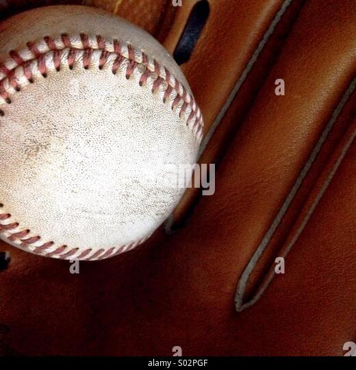 Worn baseball and glove. - Stock Image