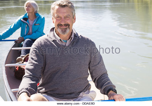 Portrait of mature couple canoeing - Stock Image
