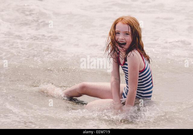 Laughing girl (6-7) sitting on beach - Stock Image