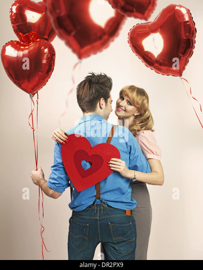 Fall in love among lots of heart balloons - Stock Image