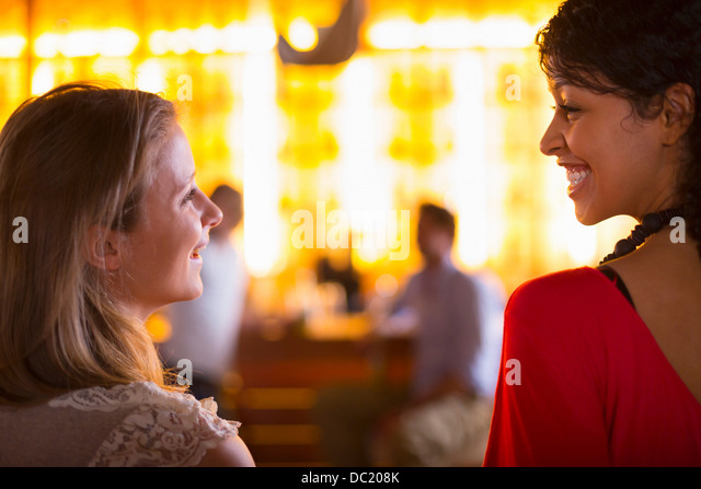 Two young females talking in bar - Stock Image