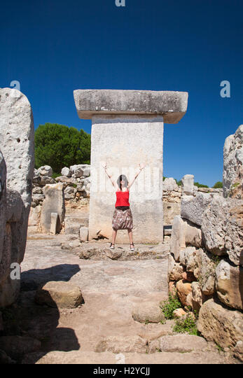 woman tourist greeting arms up in prehistoric monument named Taula from Talayotic times in X century Before Christ, - Stock Image