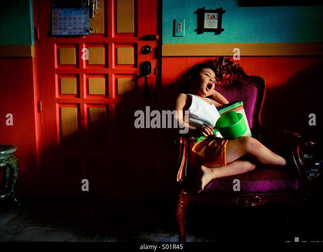Sleepy child on a chair - Stock Image