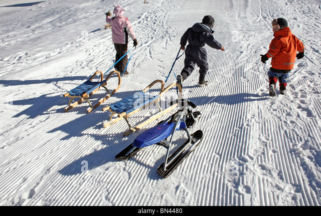Children pulling sleds on the snow, Jerzens, Austria - Stock Image