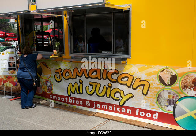 Woman ordering from a Jamaican food truck in downtown Vancouver, British Columbia, Canada - Stock Image