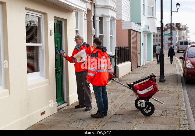 Two postmen with two wheeled postal trolley delivering post on city street. - Stock Image