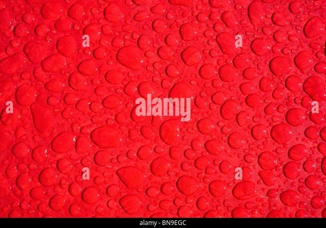 Close up macro photograph of rain drops on a red table - Stock Image