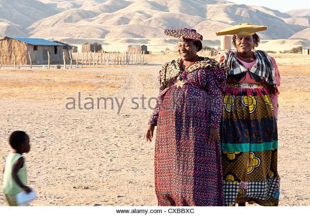 Two Herero woman in traditional dress and horned hats, Purros village, Kaokoland wilderness region, Namibia, Africa - Stock Image