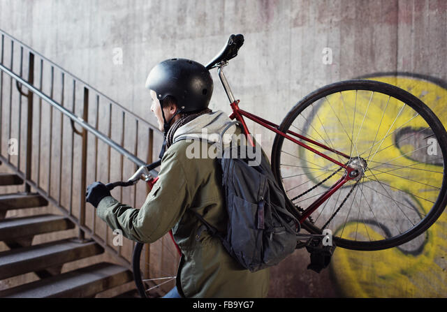 Sweden, Sodermanland, Stockholm, Sodermalm, Slussen, Mid adult man carrying bicycle upstairs - Stock Image