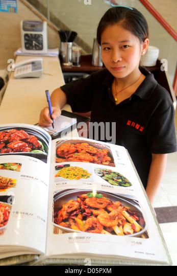 Shanghai China Yangpu District Siping Road restaurant menu Mandarin symbols hanzi Asian woman waitress taking order - Stock Image