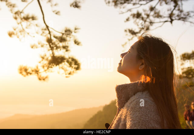 closeup woman face feeling fresh with sunrise in the morning - Stock Image