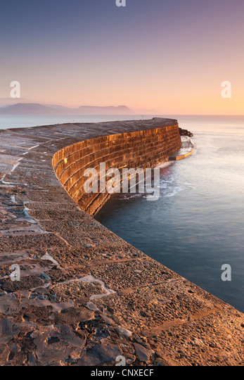 The historical Cobb stone harbour wall at Lyme Regis, Dorset, England. Winter (December) 2010. - Stock Image