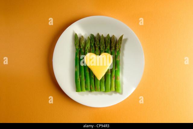 Butter heart melting on asparagus spears - Stock-Bilder