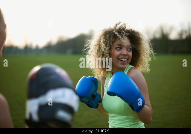 Two women exercising with boxing gloves in the park - Stock Image