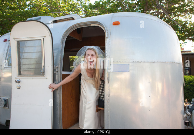 Bride screaming with excitement inside an Airstream trailer. - Stock Image