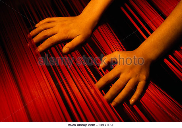 A woman's hands working on a loom at a textile factory. - Stock Image
