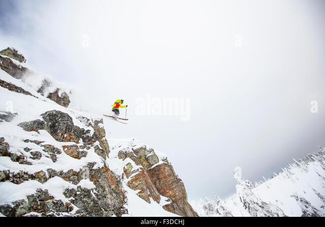 Skier jumping off rocky mountain - Stock-Bilder