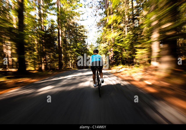 A female cyclist quickly rides on a small narrow road near Franconia, New Hampshire.  Motion Blur. - Stock Image