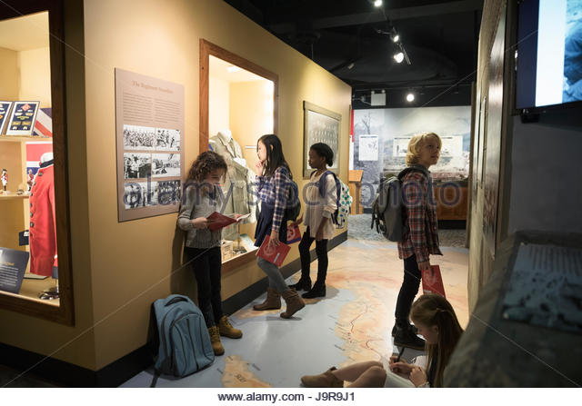 Multi-ethnic students looking at exhibits on field trip in war museum - Stock-Bilder