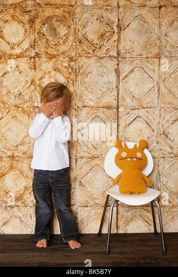 Boy hiding from stuffed animal - Stock-Bilder