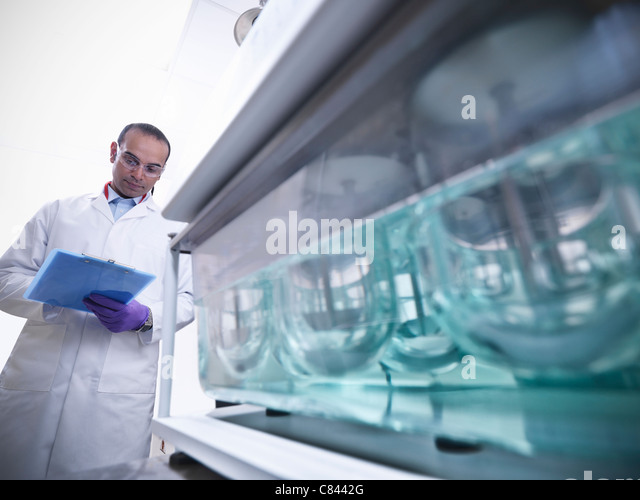 Scientist working on equipment in lab - Stock Image