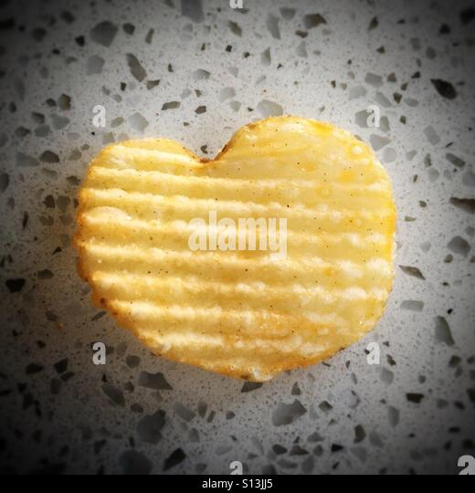 A heart-shaped potato chip. Love! - Stock Image