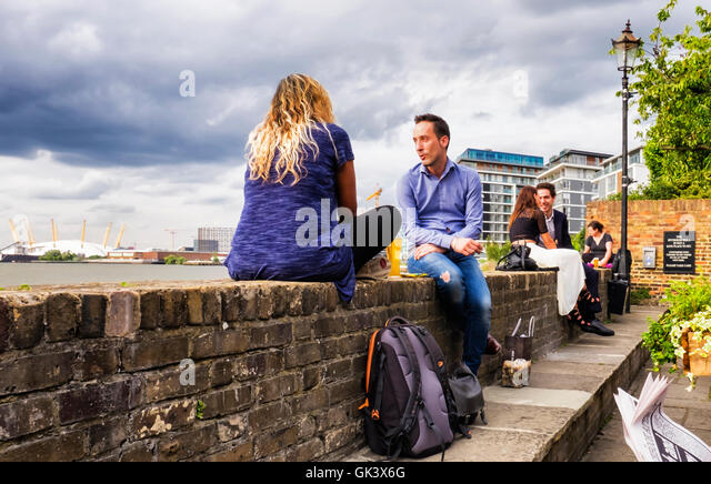 Young couples enjoy a drink after work at riverside pub after work, Greenwich, London - Stock Image