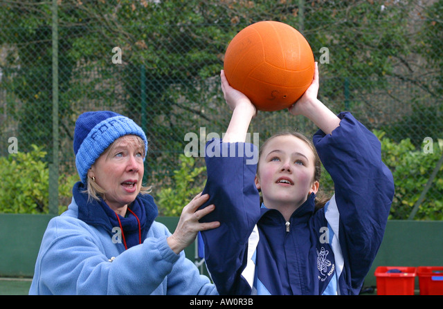 Teacher and pupil netball shooting - Stock Image