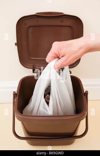 UK. Person lifting plastic bag of household food waste out of indoor food waste bin inside - Stock Image