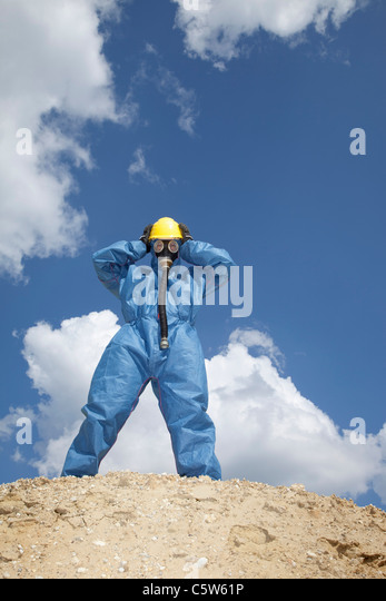 Germany, Bavaria, Man in protective workwear standing on top of sand dune - Stock Image