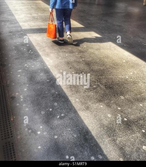 Woman walking with a orange bag - Stock Image