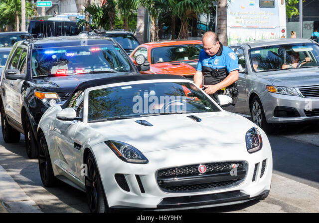 Florida Miami Beach police policeman writing ticket traffic giving driver sports car - Stock Image